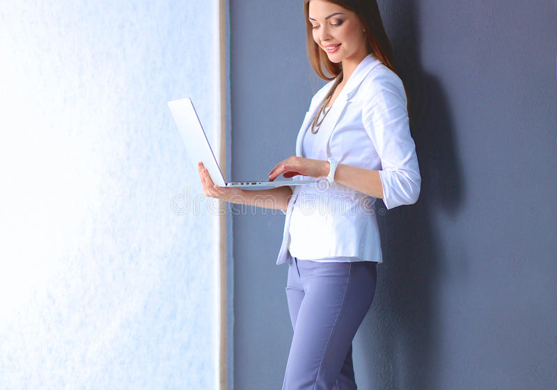 Young woman holding a laptop, standing on gray background.  royalty free stock images