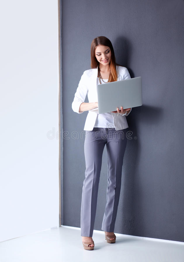 Young woman holding a laptop, standing on gray background.  royalty free stock photo