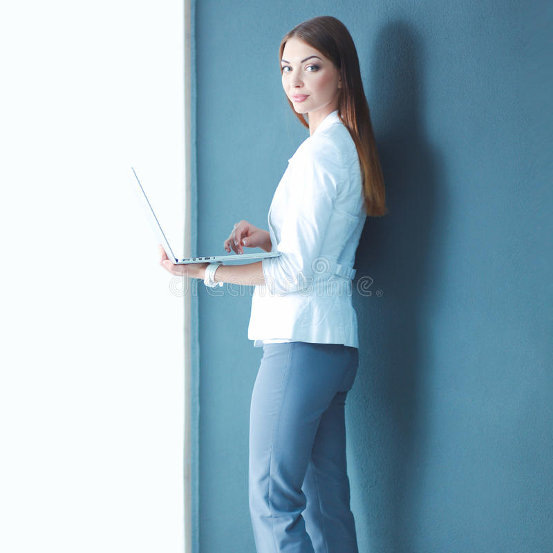 Young woman holding a laptop, standing on gray background.  stock photography