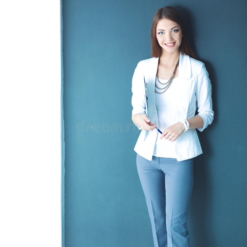 Young woman holding a laptop, standing on gray background.  royalty free stock photos