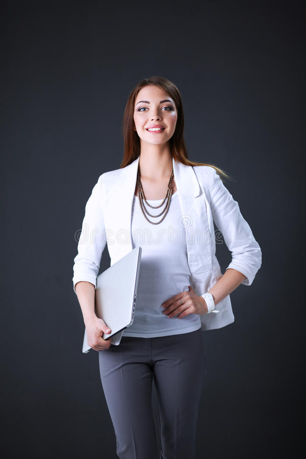 Young woman holding a laptop, standing on gray background.  stock photo