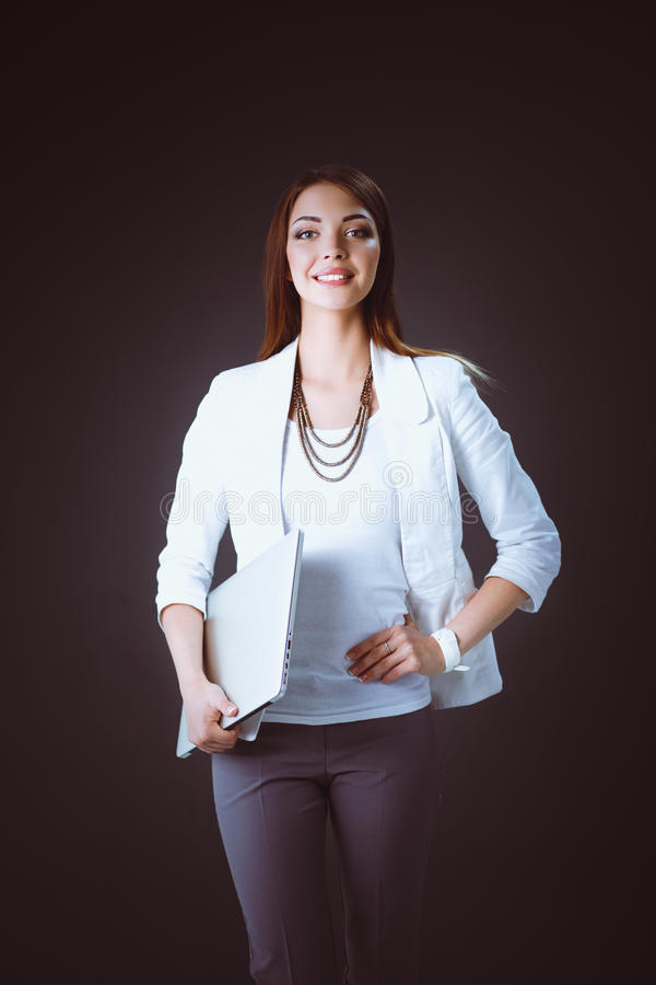 Young woman holding a laptop, standing on gray background.  royalty free stock photography