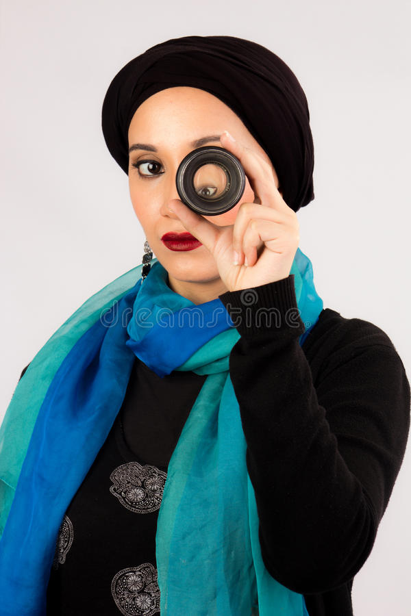 Young Woman holding a lens in hijab and colorful scarf royalty free stock photos