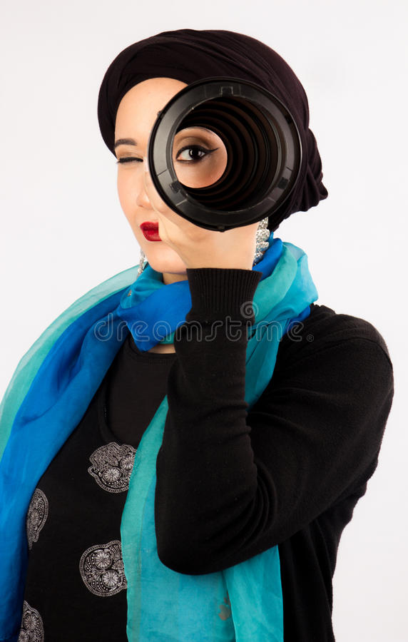 Young Woman holding a lens in hijab and colorful scarf royalty free stock images