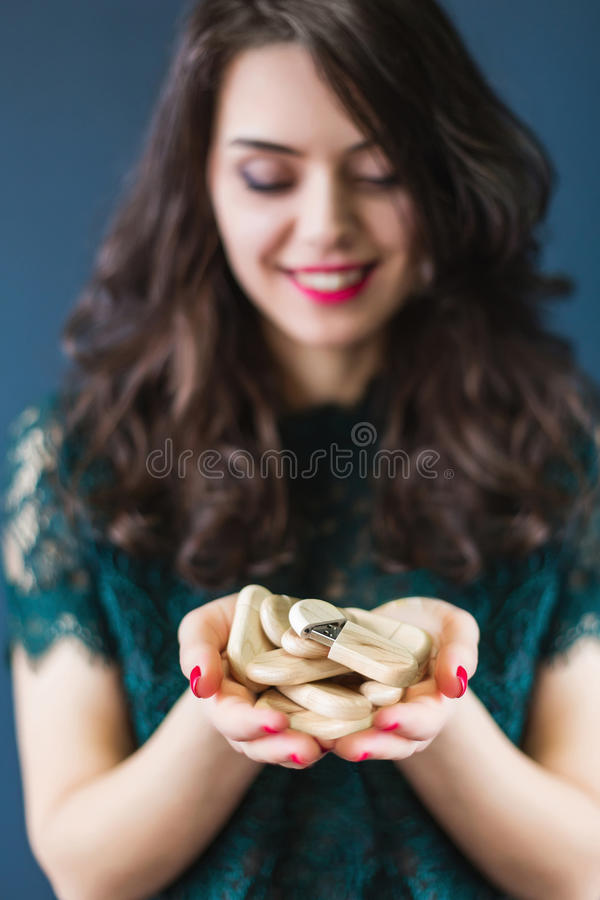 Young woman holding a lot of usb sticks. Young woman holding a lot of wooden usb sticks in hands royalty free stock images