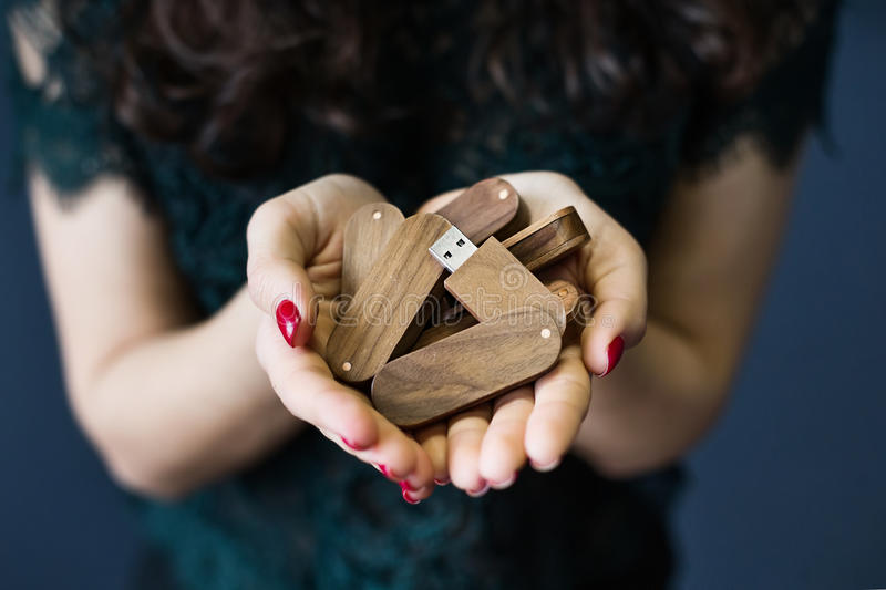 Young woman holding a lot of usb sticks. Young woman holding a lot of wooden usb sticks in hands royalty free stock photography