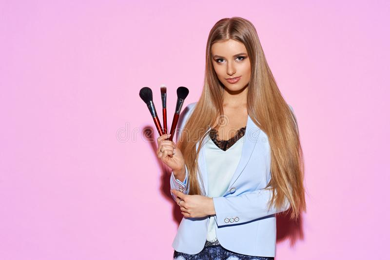 Young woman holding makeup brushes royalty free stock photo