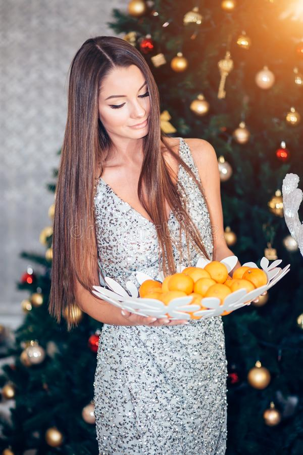 Young woman holding mandarin near a Christmas tree. New year, holiday, health concept. Girl in dress looking down stock images