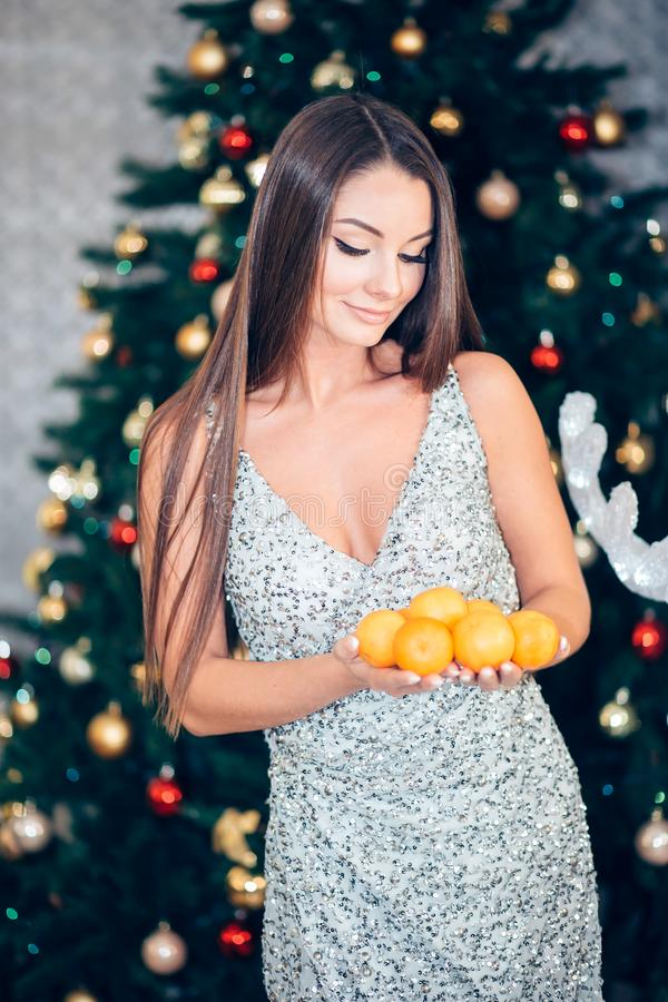 Young woman holding mandarin near a Christmas tree. New year, holiday, health concept. Girl in dress looking down royalty free stock photos