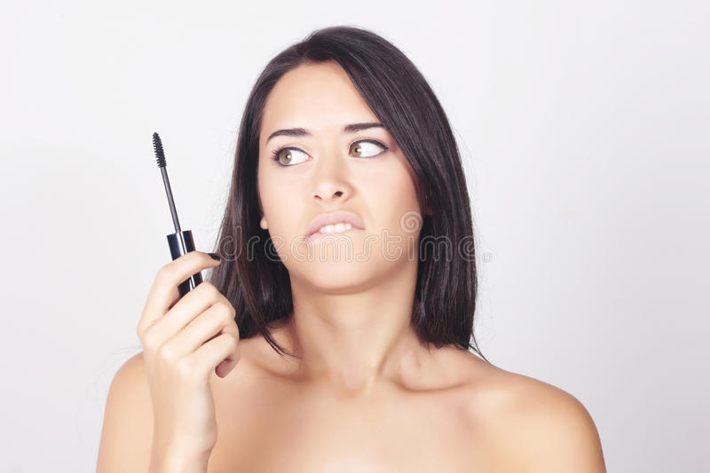 Young woman holding mascara for her eyelashes stock images