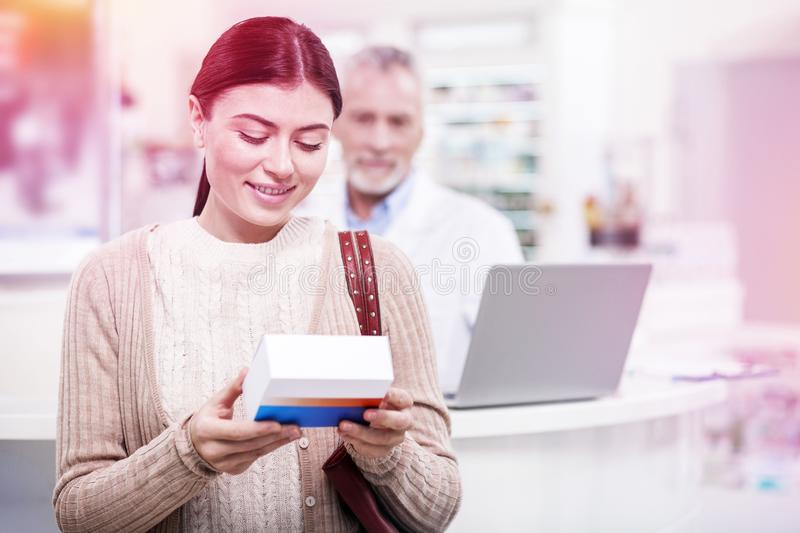 Young woman holding a medicine and reading the instruction. Investigating the medicine. Young dark-haired women holding a medicine and reading the instruction royalty free stock image