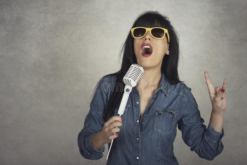 Young woman holding a microphone singing royalty free stock images