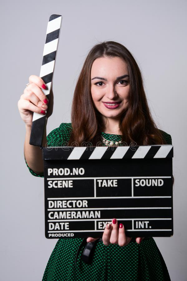 Young woman holding a movie clapper. Cheerful girl in green dress helps in shooting a movie royalty free stock images
