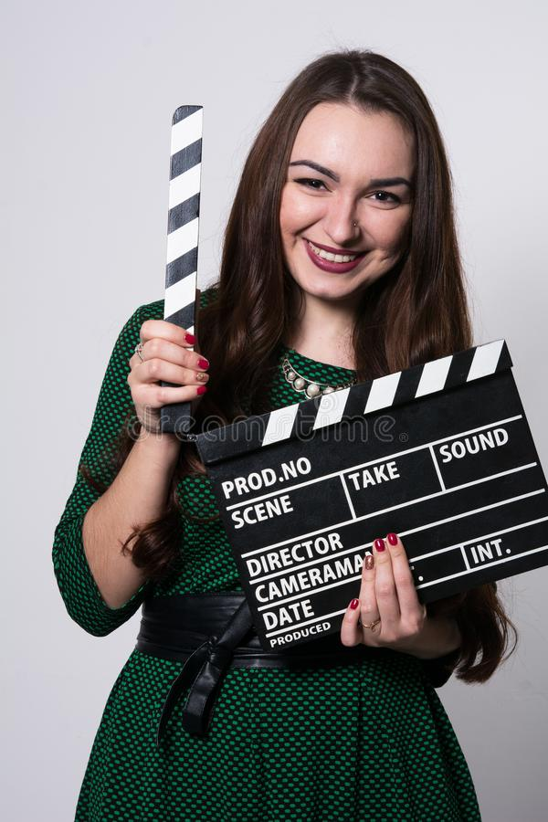 Young woman holding a movie clapper. Cheerful girl in green dress helps in shooting a movie royalty free stock image