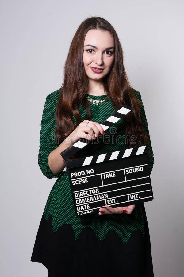 Young woman holding a movie clapper. Girl in green dress helps in shooting a movie royalty free stock photo