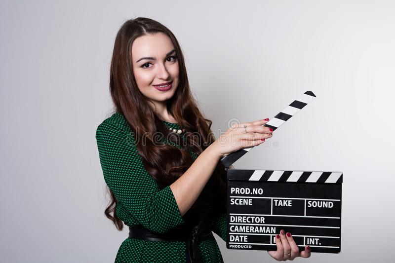 Young woman holding a movie clapper. Girl in green dress helps in shooting a movie stock photos
