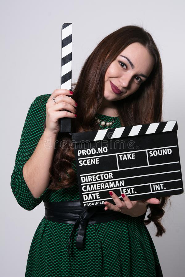 Young woman holding a movie clapper. Girl in green dress helps in shooting a movie stock photo