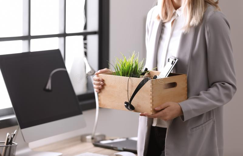 Young woman holding moving box with office stuff indoors royalty free stock images