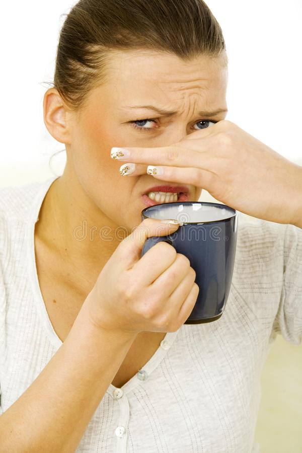 Young woman holding a mug with a disgusting drink stock image