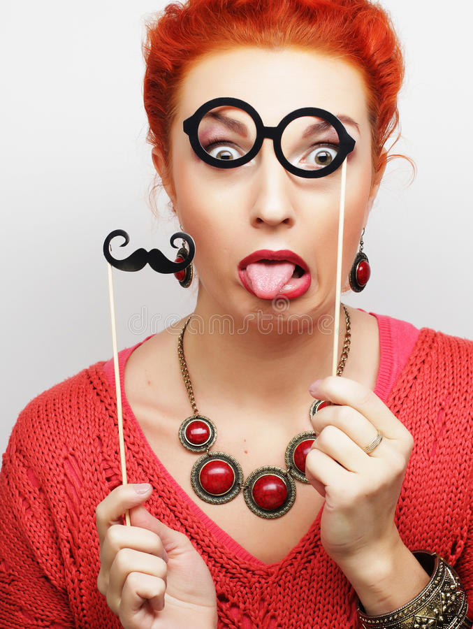 Young woman holding mustache and glasses stock photos