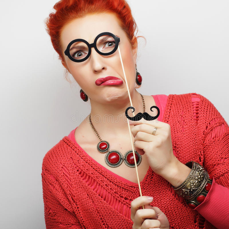 Young woman holding mustache and glasses royalty free stock photography