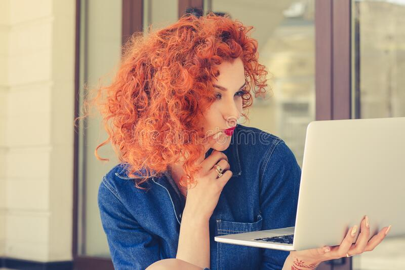 Young woman holding notebook, looking skeptical to screen, touching chin with hand, sitting outdoor. Portrait in profile of pretty royalty free stock image