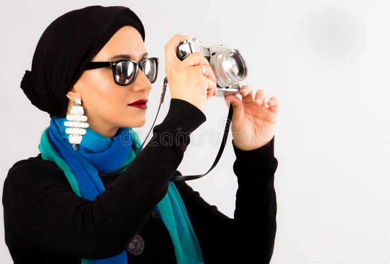 Young Woman holding old camera in hijab and colourful scarf stock image