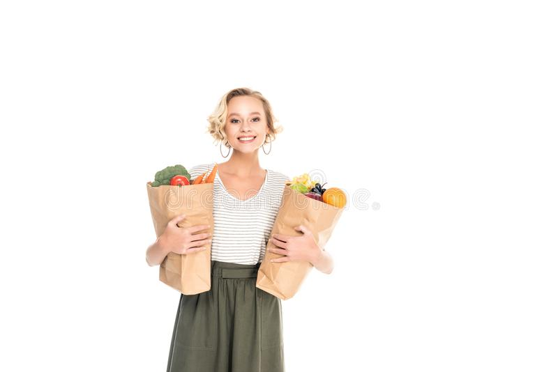 Young woman holding paper bags with fruits and vegetables and smiling at camera. Isolated on white stock photography