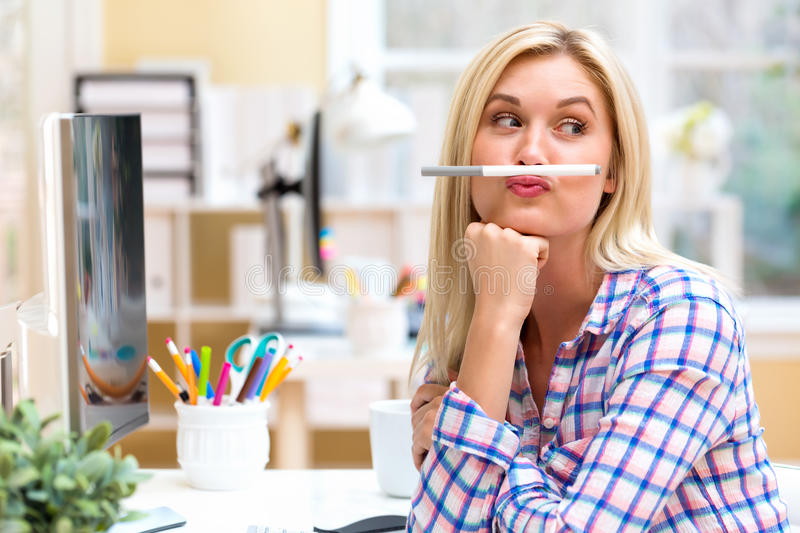 Young woman holding a pen above lips stock images