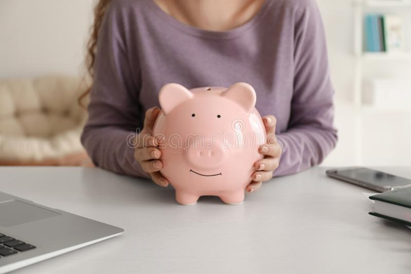 Young woman holding piggy bank indoors, closeup. Money savings concept stock images