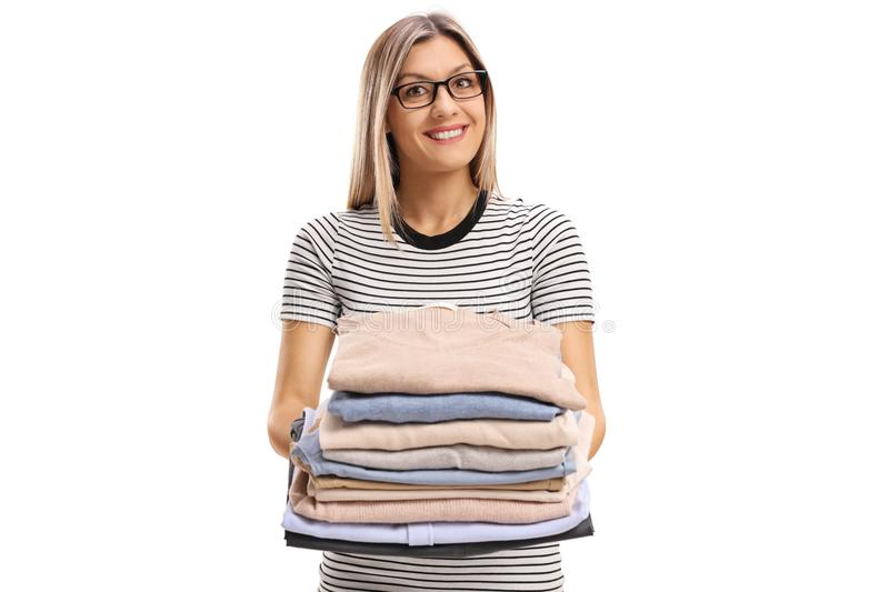 Young woman holding a pile of ironed and packed clothes. Isolated on white background royalty free stock photos