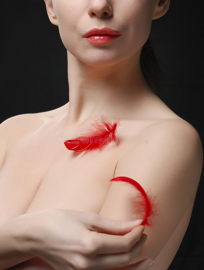 Young woman holding a plume. Young topless woman holding a plume royalty free stock image