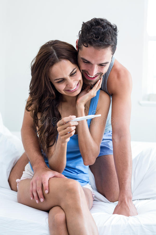 Young woman holding pregnancy test while husband embracing on bed stock image