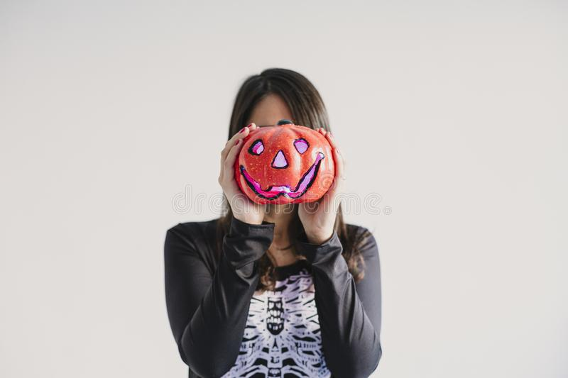 Young woman holding a pumpkin covering her face. Wearing a black and white skeleton costume. Halloween concept. Indoors. Lifestyle. Holiday, mexican, fall stock images