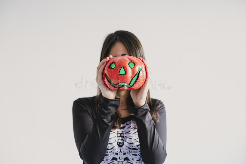 Young woman holding a pumpkin covering her face. Wearing a black and white skeleton costume. Halloween concept. Indoors. Lifestyle. Holiday, mexican, fall royalty free stock photography