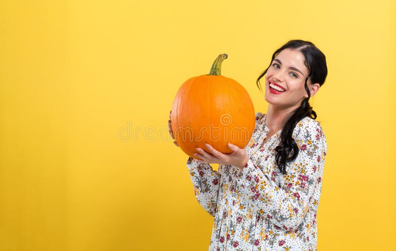 Young woman holding a pumpkin royalty free stock photo
