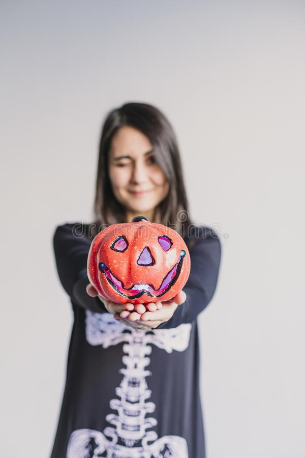 Young woman holding a pumpkin and making a wink face. Wearing a black and white skeleton costume. Halloween concept. Indoors. Lifestyle, holiday, mexican, fall royalty free stock photos