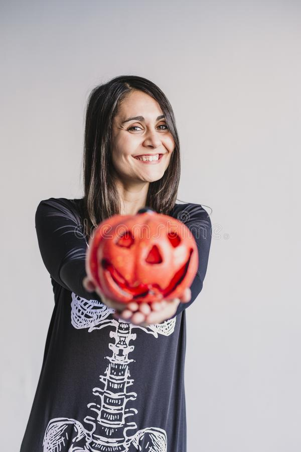 Young woman holding a pumpkin and smiling. Wearing a black and white skeleton costume. Halloween concept. Indoors. Lifestyle. Holiday, mexican, fall, spooky royalty free stock photography