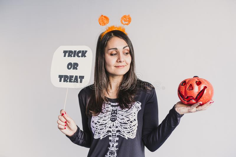 Young woman holding a pumpkin and a trick or treat sign. Wearing a black and white skeleton costume. Halloween concept. Indoors. Lifestyle, holiday, fall stock photo