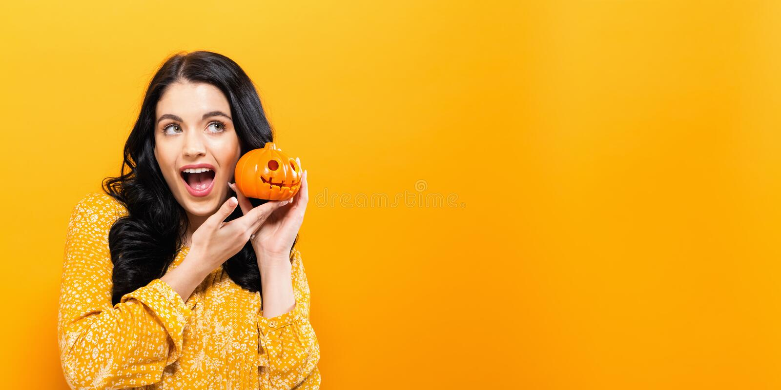 Young woman holding a pumpkin. In halloween theme royalty free stock photos