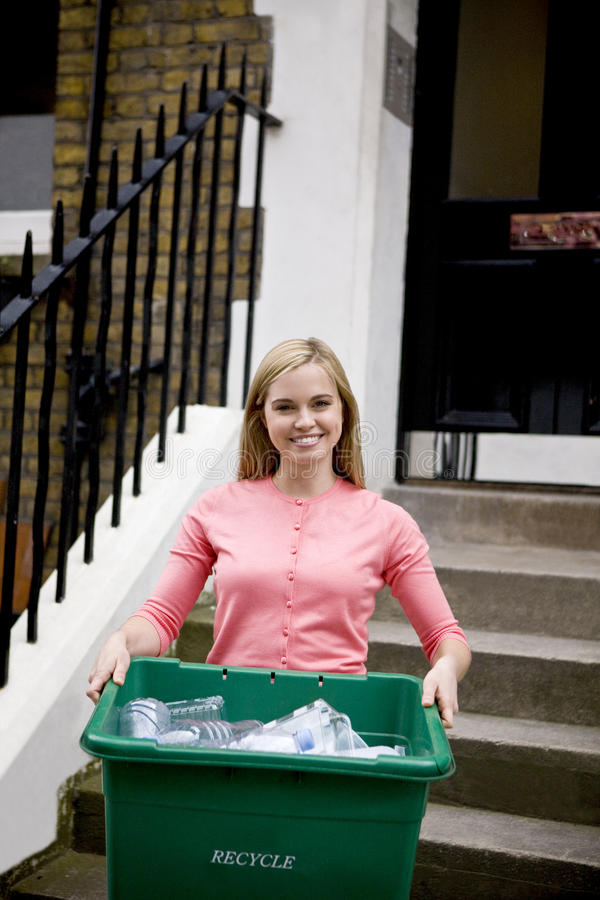 A young woman holding a recycling box, on her doorstep royalty free stock photos