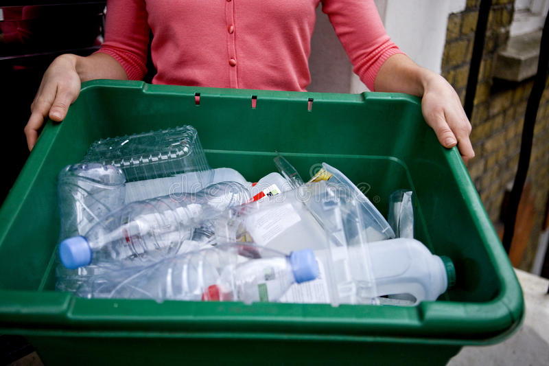 A young woman holding a recycling box, on her doorstep stock image