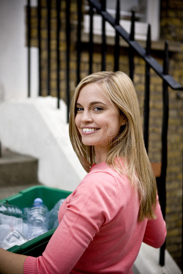 A young woman holding a recycling box, on her doorstep stock photos