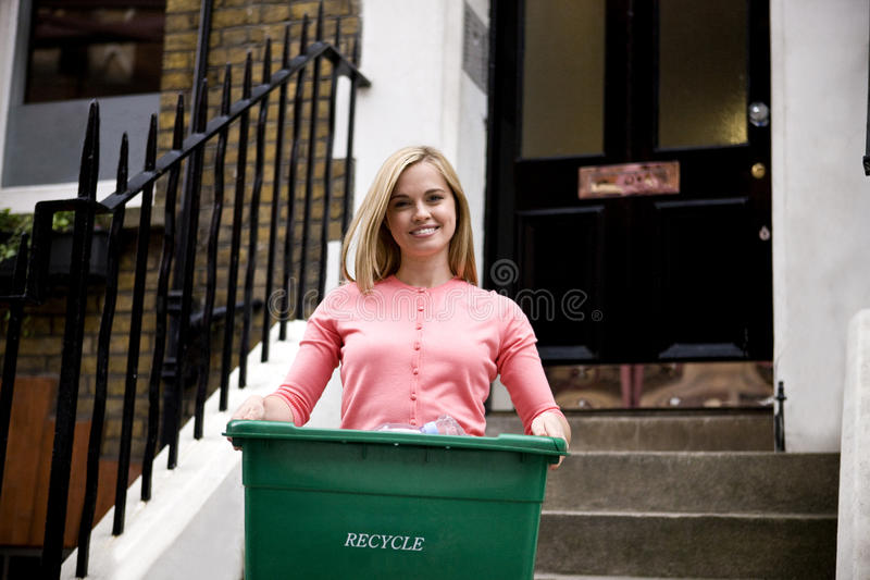 A young woman holding a recycling box, on her doorstep stock photo