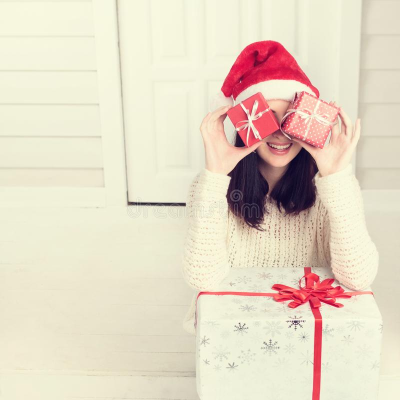 Young woman holding red Christmas gift boxes. Woman hiding her face behind boxes of Christmas gifts. Young woman holding red Christmas gift boxes stock image