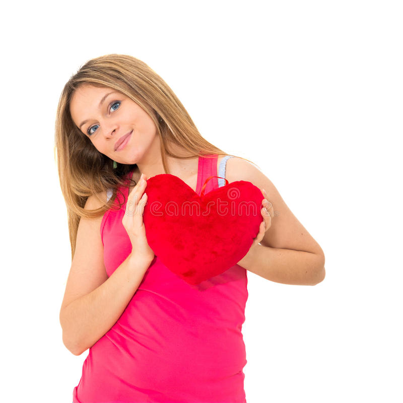 Young woman holding a red heart. Beautiful young woman holding a red heart royalty free stock photos