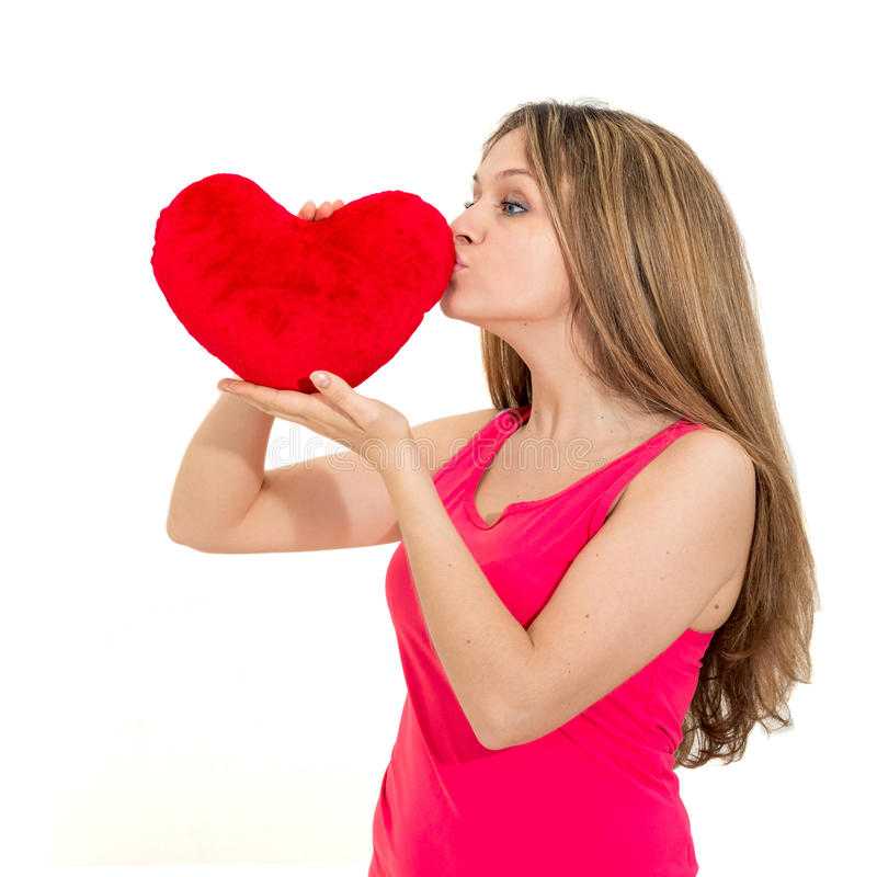 Young woman holding a red heart. Beautiful young woman kiss a red heart royalty free stock image