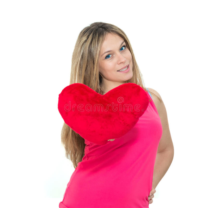 Young woman holding a red heart. Beautiful young woman holding a red heart royalty free stock photography