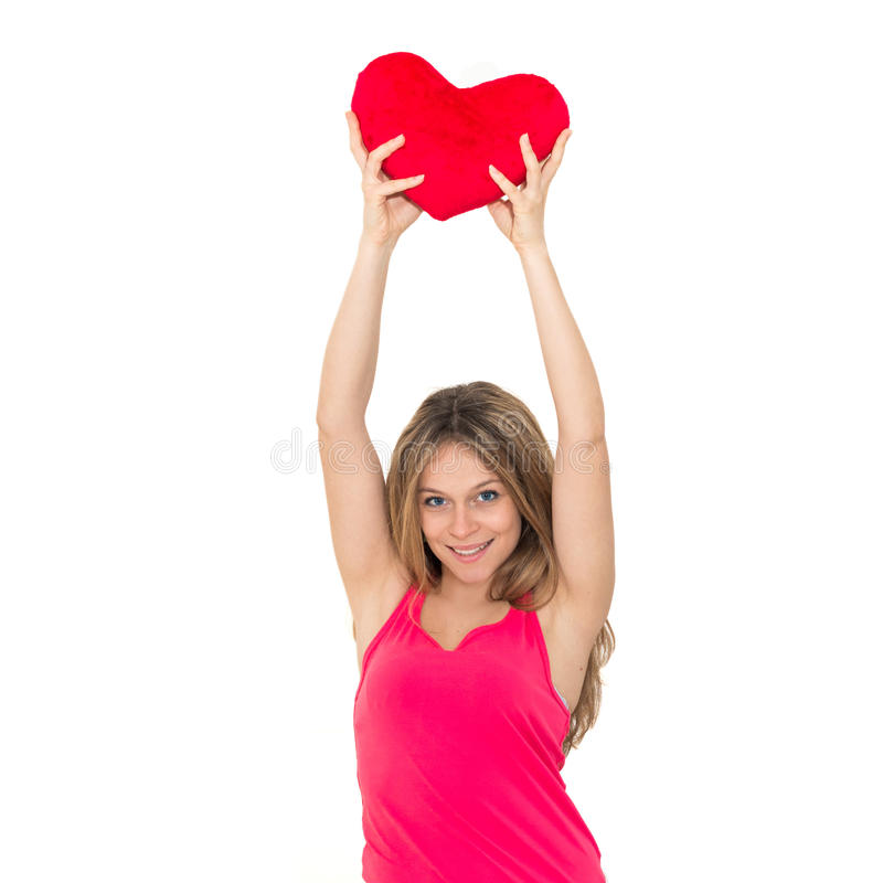 Young woman holding a red heart. Beautiful young woman holding a red heart royalty free stock images