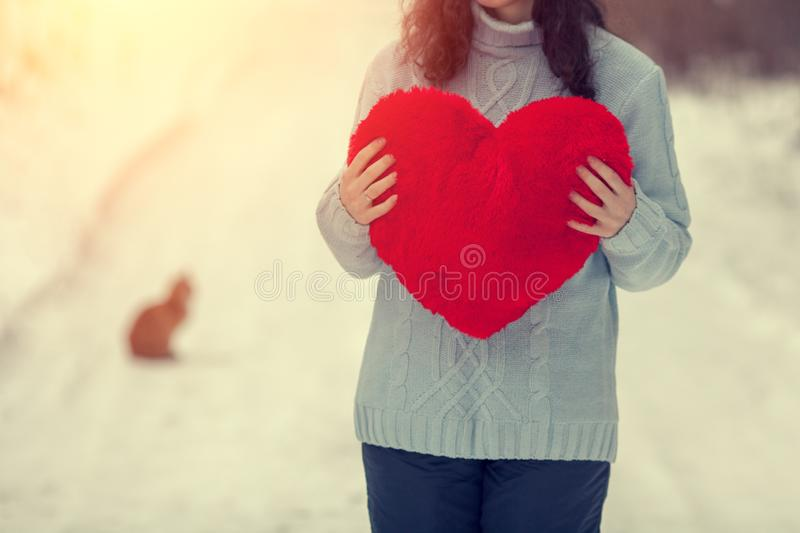 Young woman holding red heart outdoors in winter stock photo